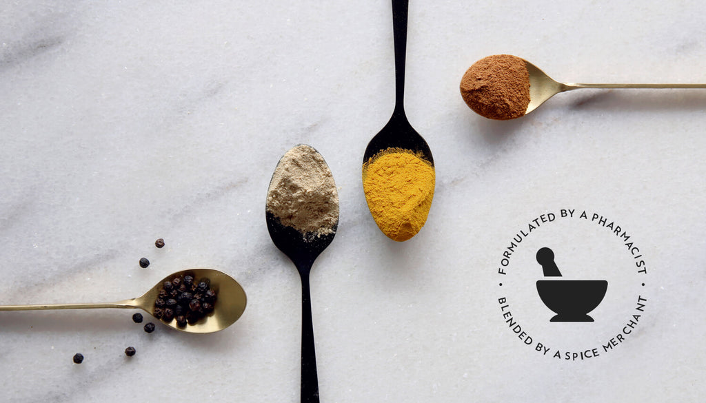 A Blend of spices turmeric, black pepper, ginger and cinnamon, displayed in spoons on a marble table.