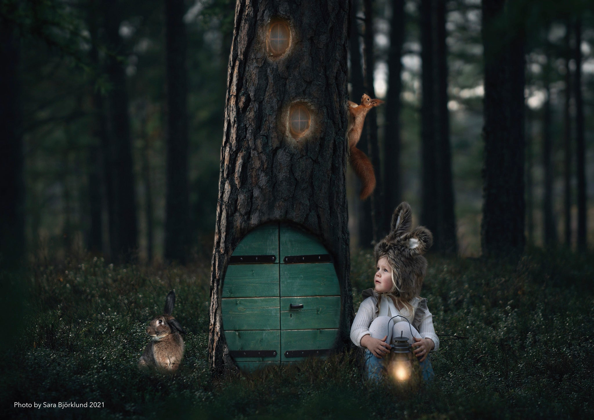 Small child with bunny ear hat sitting next to a big tree with a magic door.