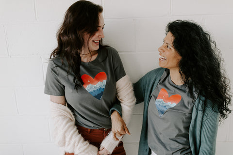 Two women wearing grey t-shirts with a heart with mountains