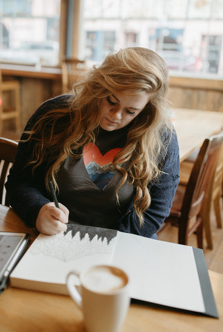 Shelby Campbell sitting in Leavenworth coffee shop wearing a grey graphic t-shirt with a heart and mountain scene illustration. PNW Style. Pacific Northwest. Drawing. Sipping Coffee. Cafe.  Leavenworth, Washington. Mountains. Mountain Style.