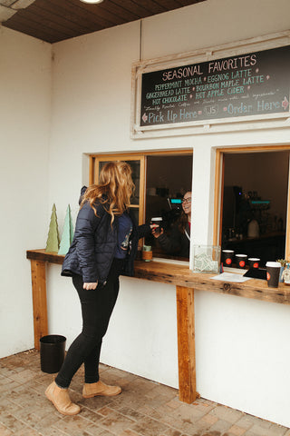 Women wearing a blue graphic t-shirt with a triangle shaped mountain illustration on the front. Black denim jeans. High Waisted. Booties. Coffee. Outdoor Coffee Shop in Leavenworth, Washington. PNW Style. Pacific Northwest.