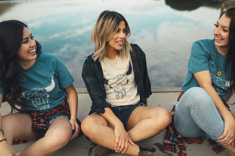 Group of women sitting in front of a small lake/pond. Wearing graphic t-shirts with a steer skull design on the front. PNW style. Wenatchee, WA. Pacific Northwest. Graphic Tee.