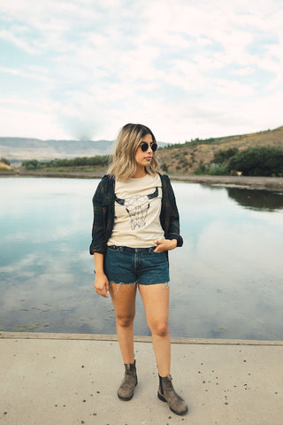 Woman standing in front of small lake/pond in Wenatchee, WA. Wearing a graphic t-shirt with a steer skull design on the front. Jeans Shorts. Round Sunglasses. Summer Time.PNW Style. Pacific Northwest.