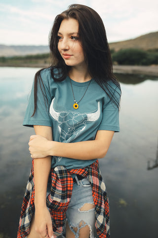 Woman standing in front of small lake/pond in Wenatchee, WA. Wearing a graphic t-shirt with a steer skull design on the front. Jeans. Flannel Shirt. Round Sunglasses. Summer Time.PNW Style. Pacific Northwest.