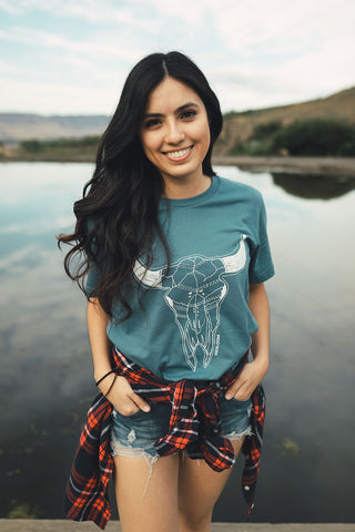 Woman standing in front of small lake/pond in Wenatchee, WA. Wearing a graphic t-shirt with a steer skull design on the front. Jeans. Flannel Shirt.  Summer Time.PNW Style. Pacific Northwest.
