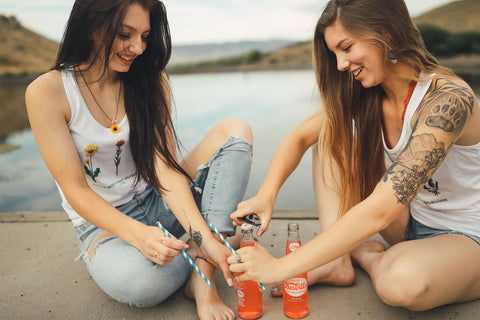 Two women sitting in front of small lake/pond opening up glass soda bottles. Wearing white tank tops with jeans and jeans shorts. Summer time. Wenatchee, Washington. PNW Style. Pacific Northwest. Mountains. Mountain Style.