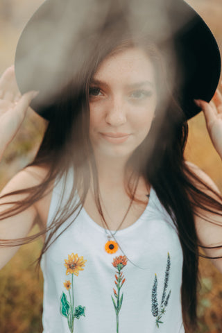 Graphic Style Tank top with Pacific Northwest Wildflowers on the front. Cute Wide Brim Hat. Field. Summer time. Golden Hour. Wearing white tank tops with jeans and jeans shorts. Summer time. Wenatchee, Washington. PNW Style. Pacific Northwest. Mountains. Mountain Style.