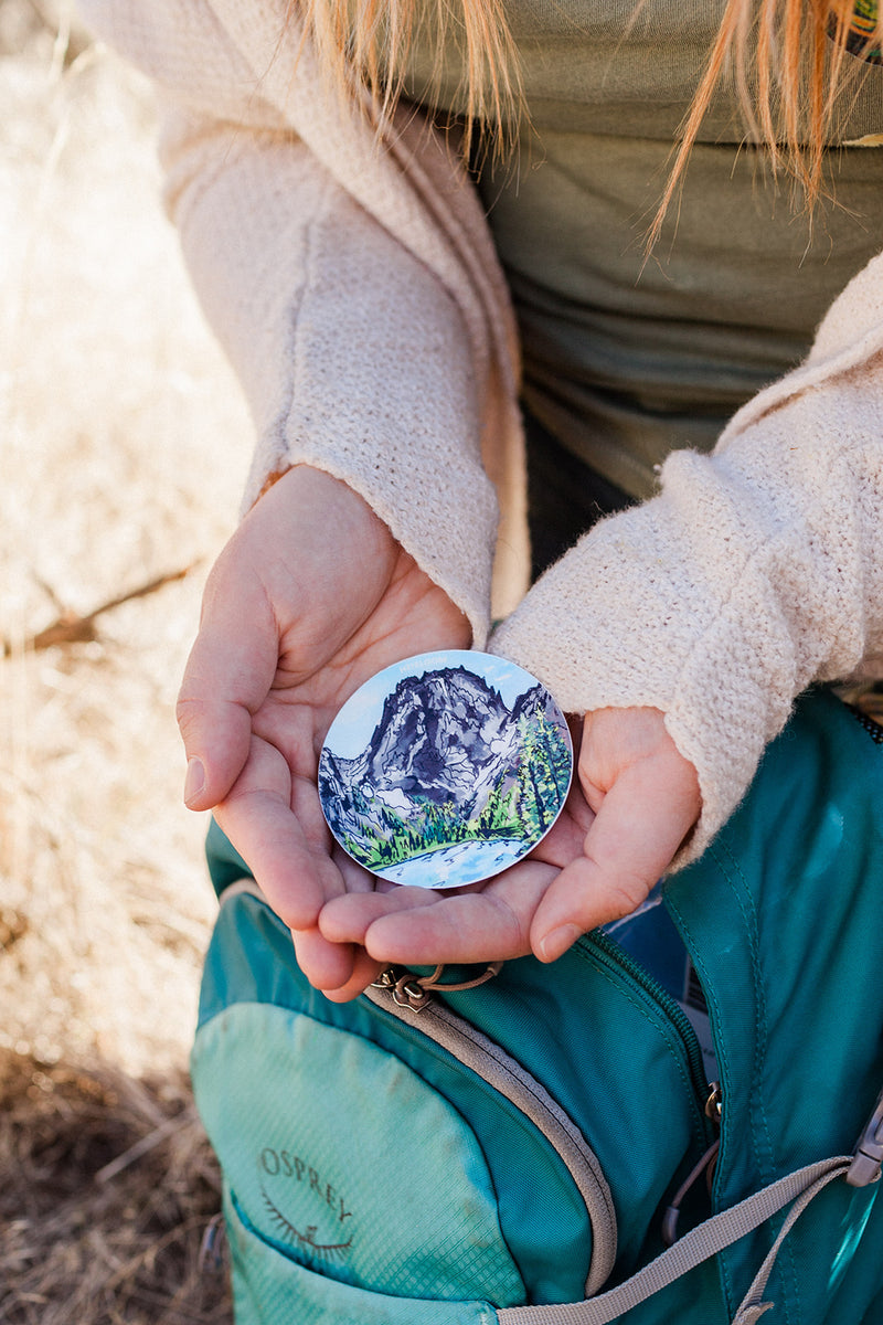 Woman holding a vinyl sticker featuring Colchuck Lake, Washington in the Pacific Northwest. You can see part of the lake and Aasgard Pass and Dragonstail Peak. It is a hand painted design that has been reprinted on to a circle Vinyl Sticker.