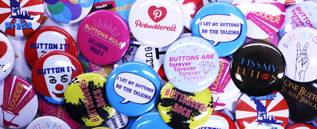 Pile of colorful pinback buttons, receive free gift with purchase