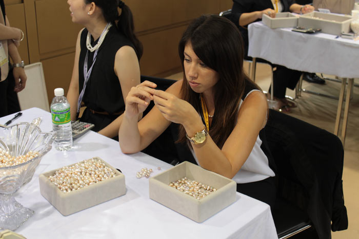 meticulously inspecting each pearl