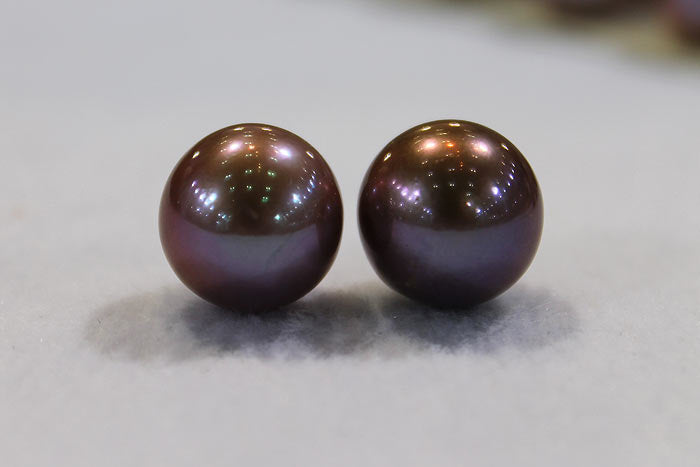 a pair of matched pearls in a deep, dark purple color