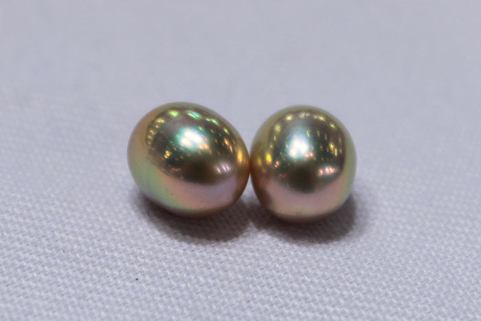 a close up of a pair of drop pearls