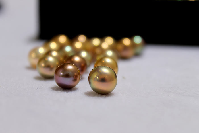 a close up of the fancy colored pearls