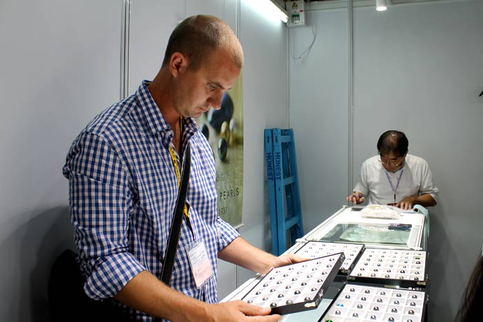 scrutinizing a tray of Tahitian pearls
