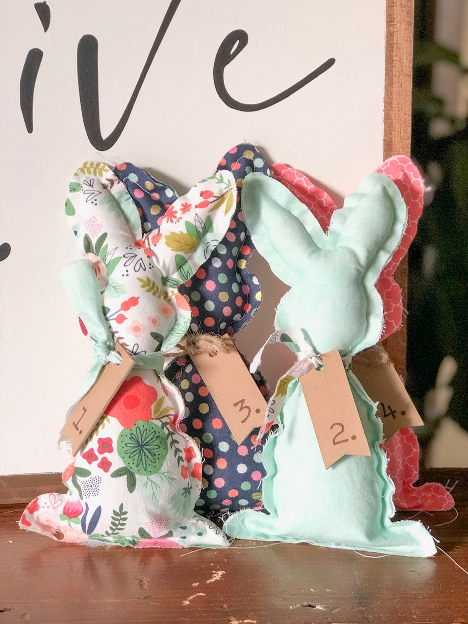 Fabric bunnies that are finished and standing on a table leaning against a wood sign