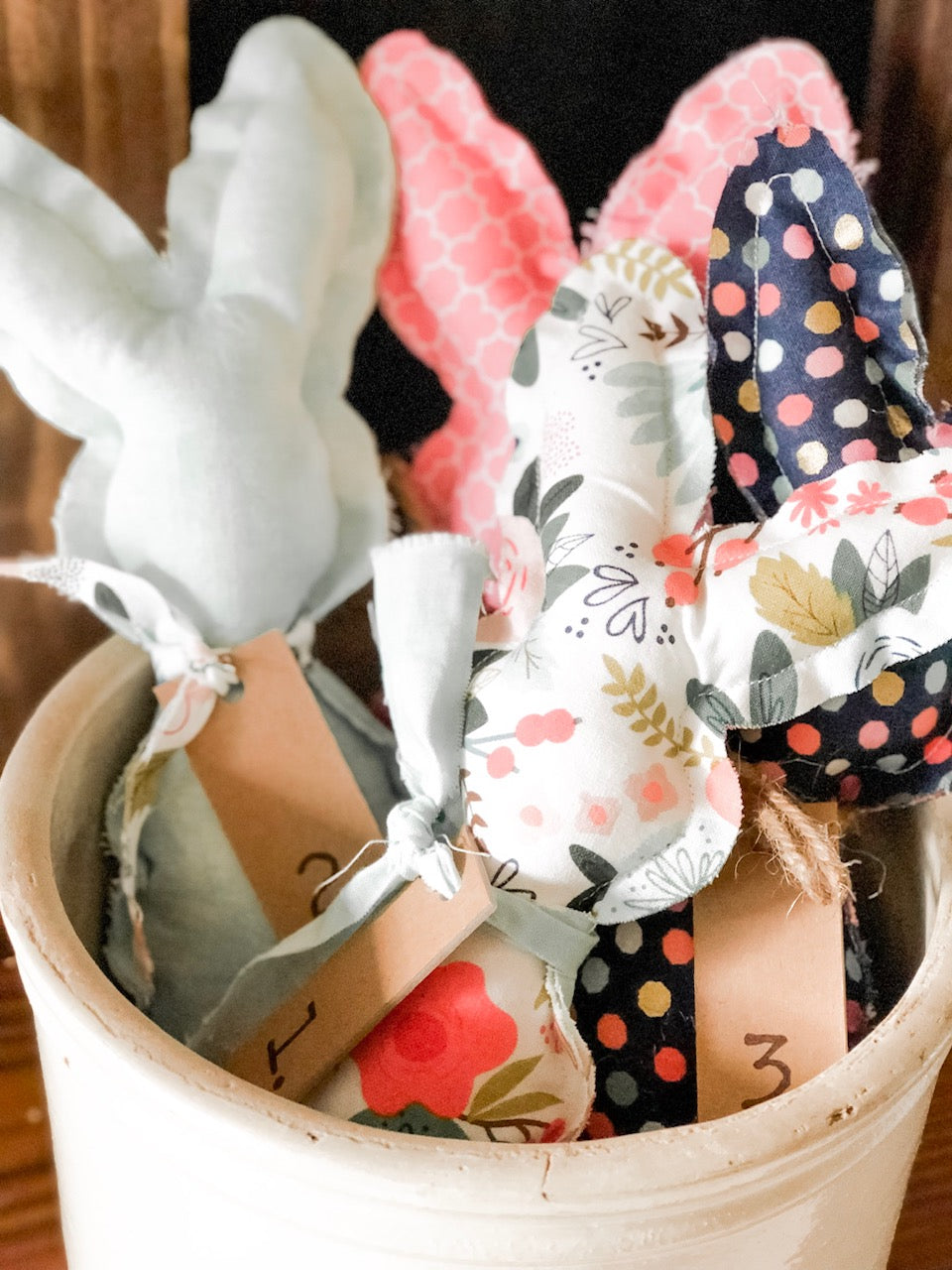 Fabric bunnies that are finished and sitting in an old crock