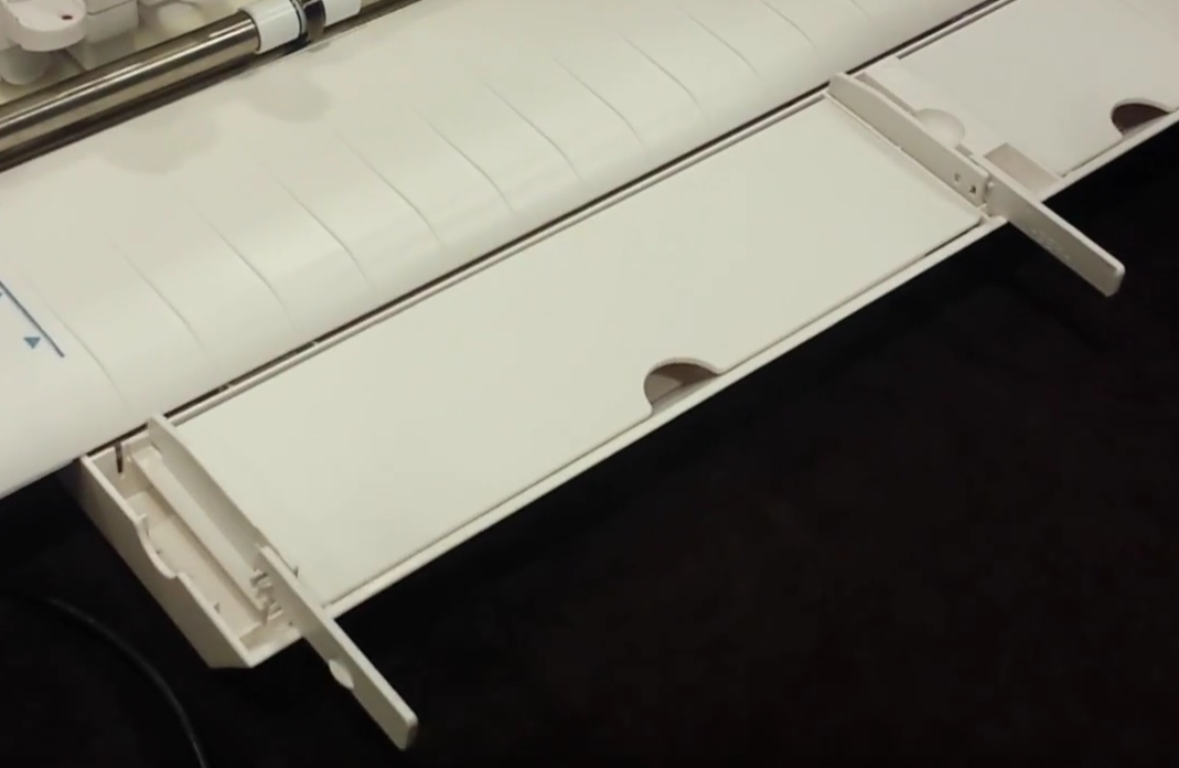 The pull out storage tray on the Cameo 3 machine has built in support bars to help support the weight of longer materials. This helps the materials from popping off the cutting mat while cutting. They fold right back into the storage tray when not in use.
