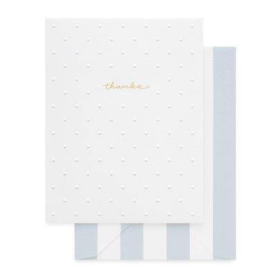 white greeting card embossed polka dot gold text says thanks white and light blue striped envelope