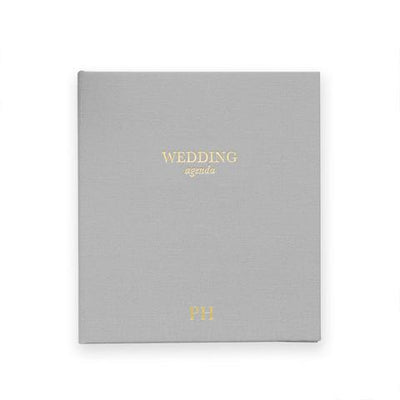 Grey cloth covered book gold text says wedding agenda
