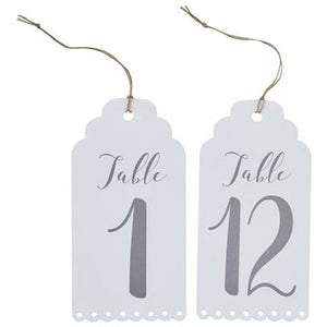 2 white eyelet edge luggage tag shaped cards with twine 1 says table 1 the other says table 12