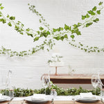 faux green foliage garland draped from ceiling above decorated dinner table
