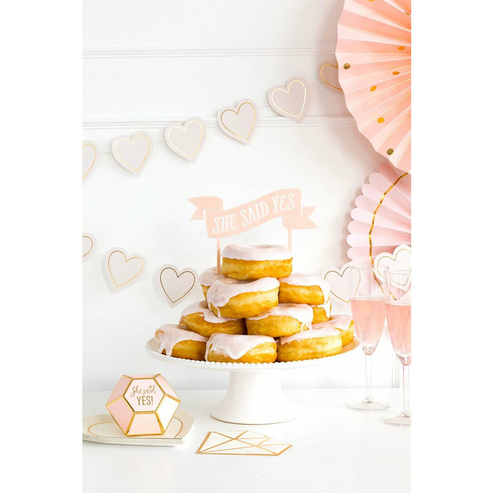 pink & gold diamond shaped favor box, party fans, banners & pink frosted donuts on a cake stand