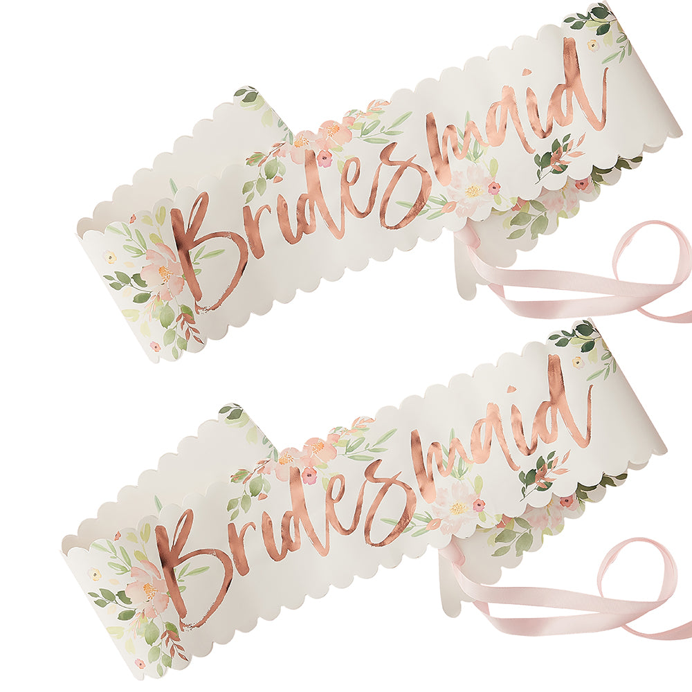 2 white paper sashes with floral allover print rose gold text says bridesmaid