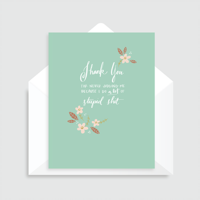 Stupid Shit mint green greeting card with white text and flower accents