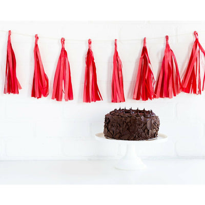 red paper tassel banner hanging on a wall above a chocolate cake on a white cake stand