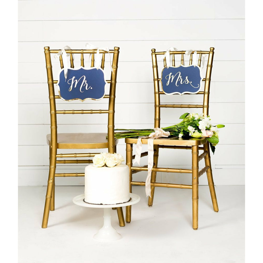2 gold chairs, each with a navy bracket shaped sign hanging from the back, 1 says mr & 1 says mrs