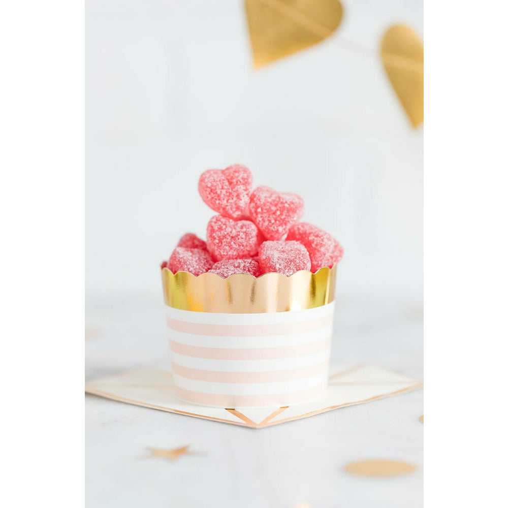 pink and white horizontal striped cupcake cup with gold foil top border filled with pink candy
