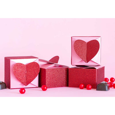 a stack of pink & red 3d heart treat boxes, red heart candies & chocolate candies on a pink table