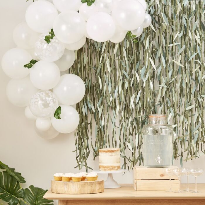 white, pearl and confetti filled balloons and sprigs of faux eucalyptus in an arch over a table