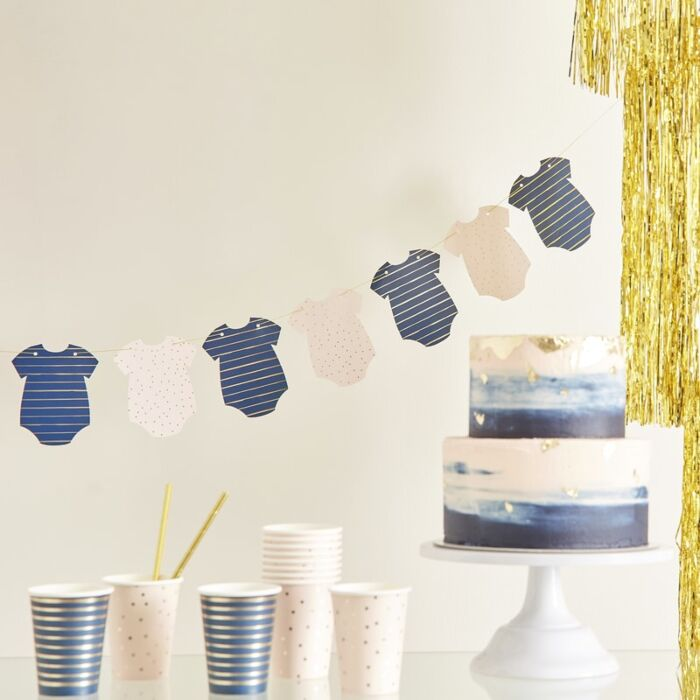 a banner of navy onesies and pink onesies, navy & pink cake & cups