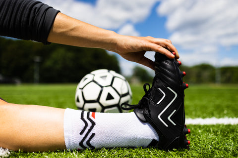 player sits on football pitch with outstretched leg and reaches for toes to stretch while wearing Ida Sports football boots
