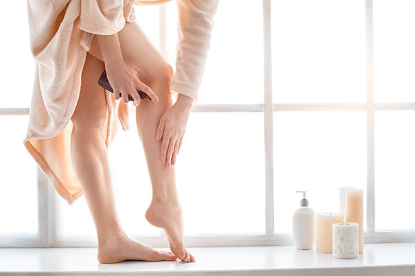 Image of woman applying body oil for mature skin on her body / legs