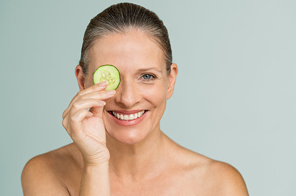 Image of mature woman holding a cucumber slice over her eye