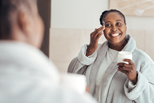 Image of Woman Using Exfoliating Cleanser in her Bathroom