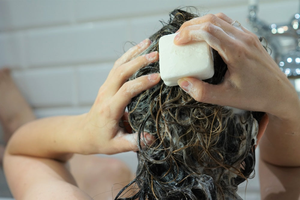 Woman washes her brown hair with homemade shampoo bar or soap, zero waste concept.