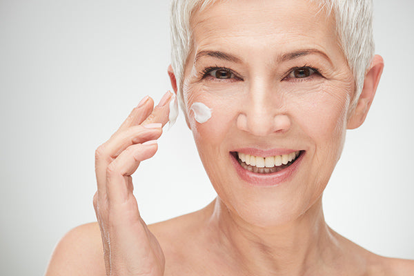 Image of laughing mature woman applying moisturiser for mature skin