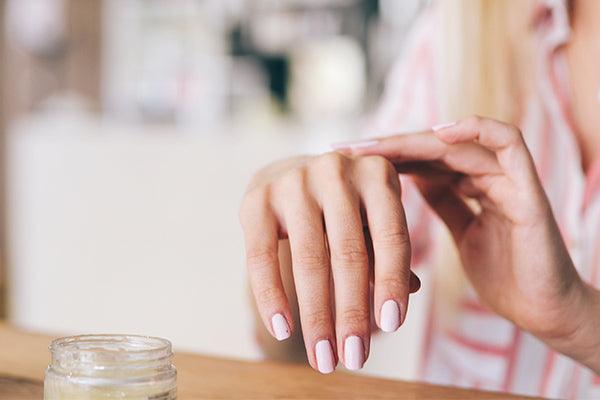 image of someone applying hand cream to reduce age spots on hands