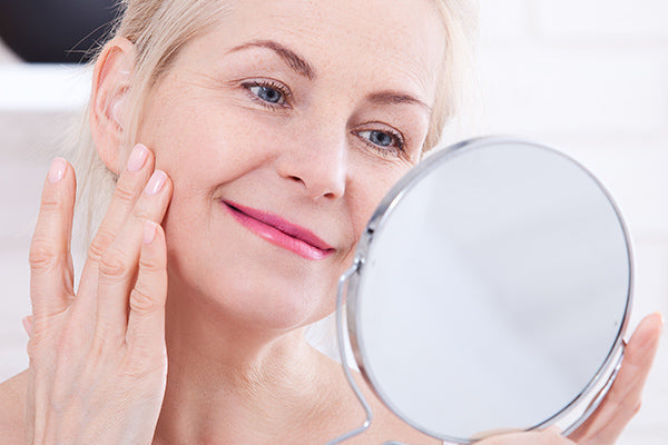 image of mature woman applying anti wrinkle facial serum with prickly pear