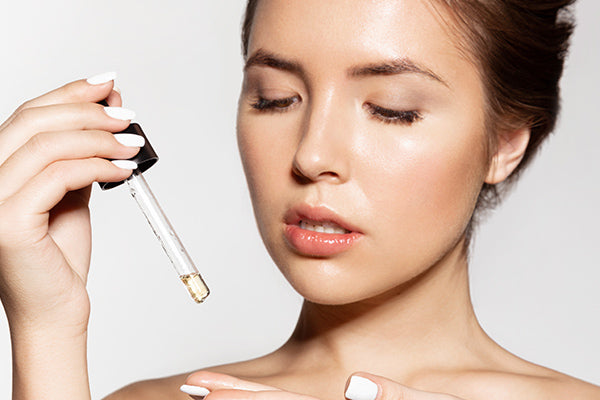 image of a woman using the facial serum with argan oil
