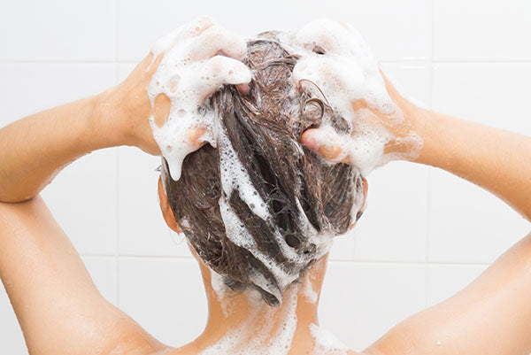 Image of woman using gentle shampoo in the shower