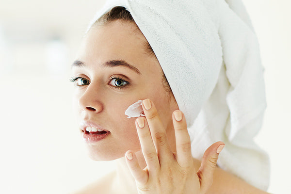 image of a woman using the lotion to improve acne damaged skin