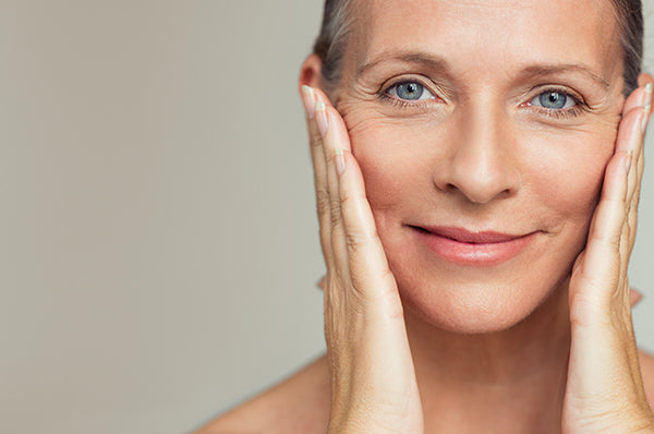 Image of woman using facial oil for mature skin