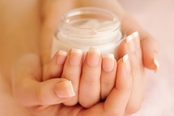 Image of a woman holding a jar of Daily Defense Rejuvenating Cream