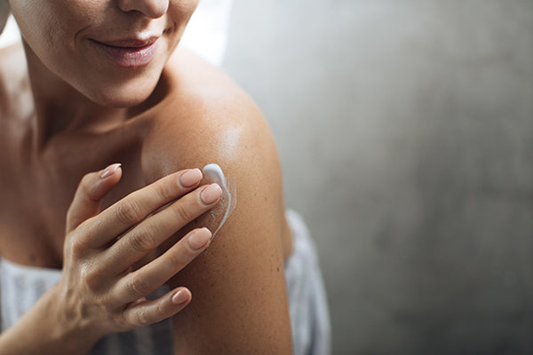 Image of a woman using the spray body lotion on her body