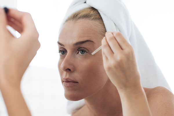 image of mature woman using facial oil suitable for skin prone to spider veins
