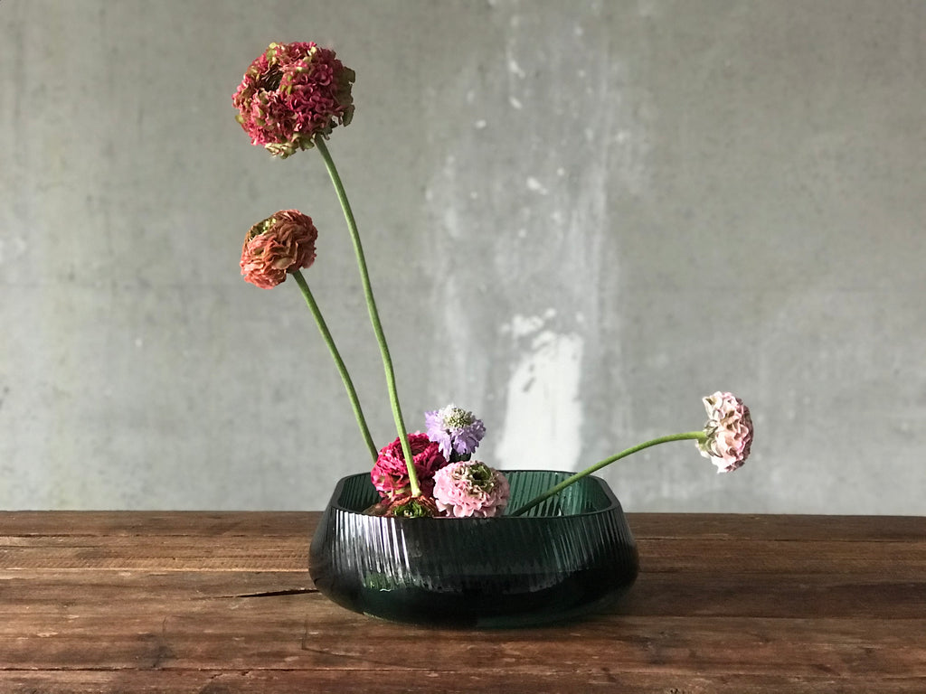 NUDE Glass Opti bowl with an Ikebana creation with ranoncules scabiosa Atlantis scoop